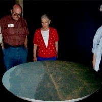 Photo of Photo of people viewing a projected image on the display table of the Griffith Observatory camera obscura built by George T. Keene.