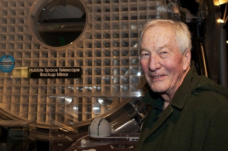 Photo of George T Keene standing next to the Hubble backup mirror at the Smithsonian.